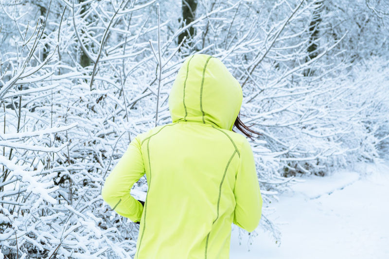 Rear view of woman standing in snow