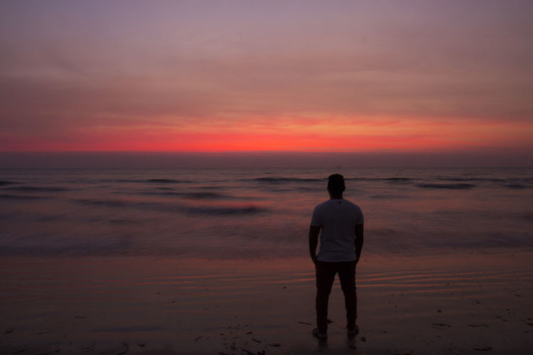 Rear view of silhouette man standing at beach against cloudy sky during sunset