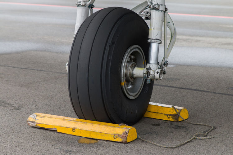 Closeup of aircraft front gear, tire with yellow chocks Apron Plane Aircraft Airplane Aviation Choke Nose Wheel Parked Parking Rubber Tie Down Tire Transportation Wheel Yellow