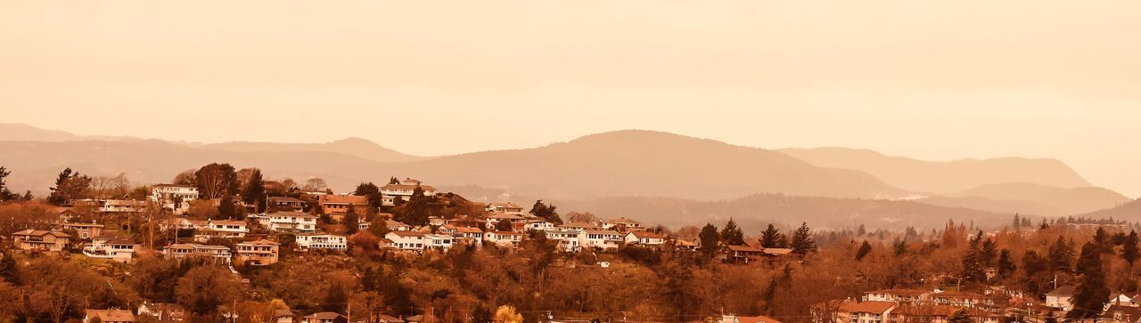 Panoramic shot of townscape by mountains against clear sky