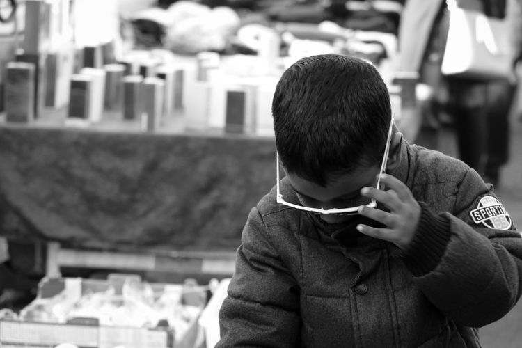 Close-up of boy using mobile phone outdoors