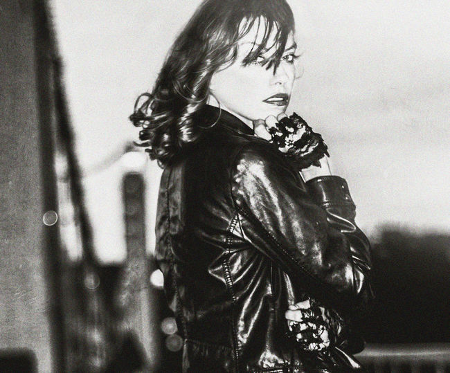 Portrait Of Young Woman Wearing Leather Jacket Against Sky