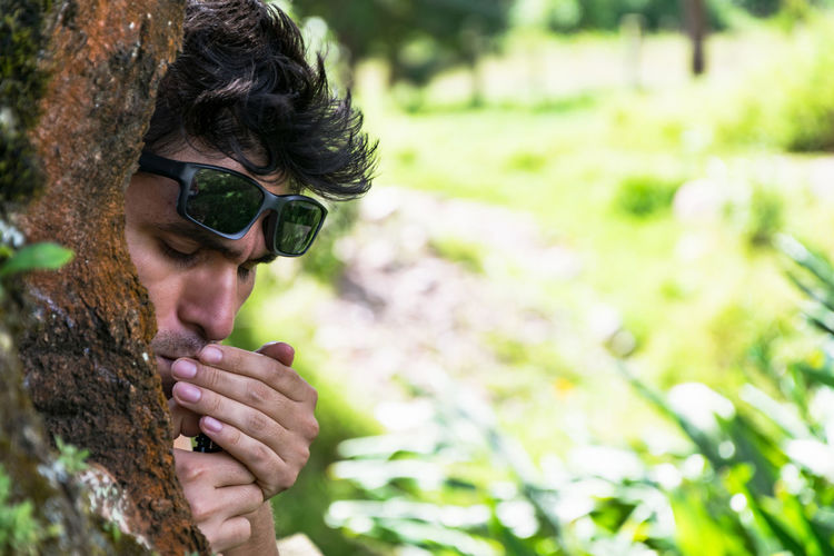Close-up of man smoking behind tree in forest