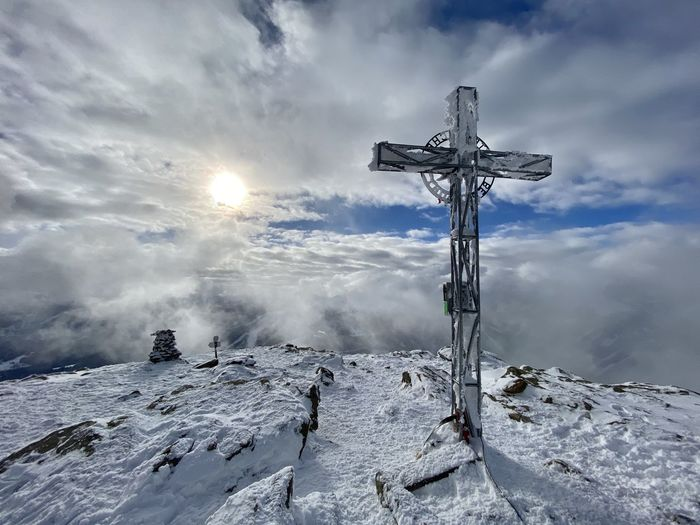View of cross on snow covered land against sky
