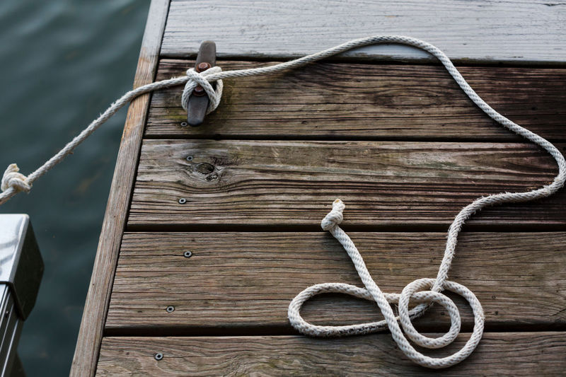High angle view of rope tied on cleat at pier