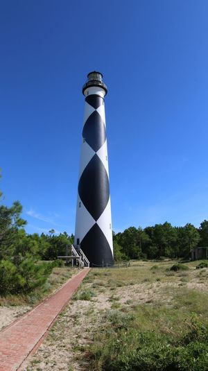 The Cape Lookout Lighthouse, 163- foot high lighthouse located on the Southern Outer Banks of North Carolina. It is one of the few lighthouses that operate during the day. It is the only structure in the United States to bear the checkered daymark, to show direction. The center of the black diamonds point in a north-south direction, while the center of the white diamond points east-west. EyeEM Photos JustGPhotos Color Palette Eyeemphoto A Bird's Eye View Interior Style Lighthouses Cape Lookout North Carolina Outer Banks