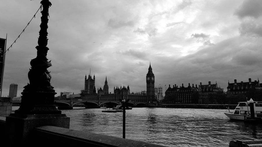 Thames river by big ben against cloudy sky in city