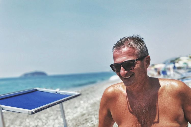 Happy shirtless senior man wearing sunglasses at beach during summer