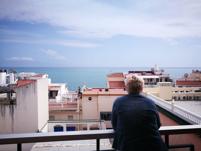 Rear view of man looking at sea from balcony
