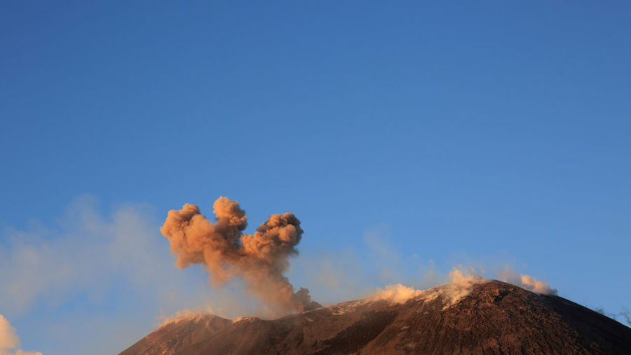 Low angle view of smoke emitting from volcanic mountain against blue sky