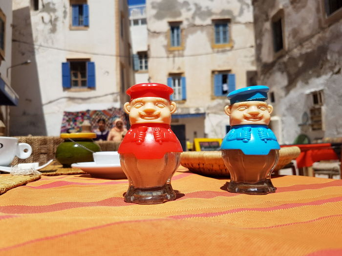 Salt and pepper shakers on tablecloth against building during sunny day