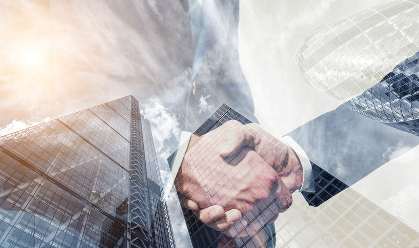Multiple Exposure Of Businessmen Shaking Hands And Buildings