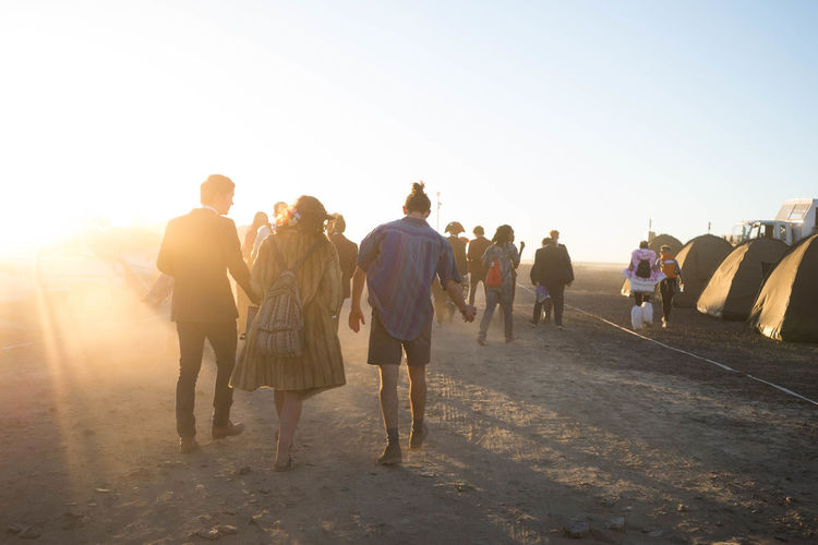 Rear view of people walking on street against clear sky