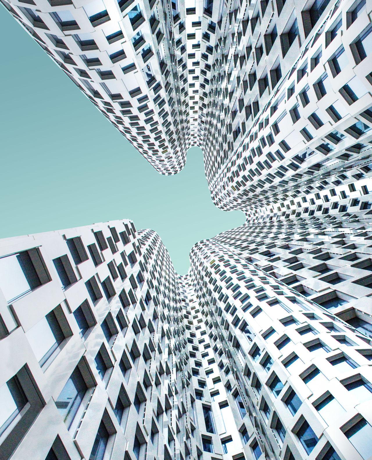 DIRECTLY BELOW VIEW OF MODERN BUILDINGS AGAINST BLUE SKY