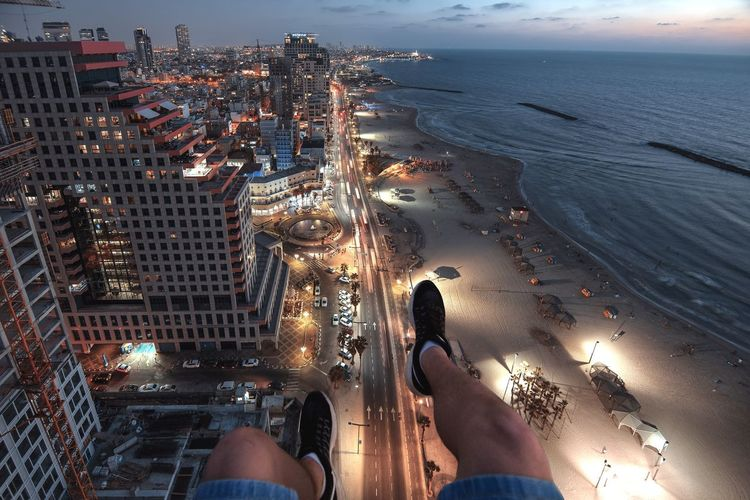 A man sits on the edge of a construction crane, his legs the man, the embankment of the city of Tel Aviv at sunset, in blue lights on the the right is the Mediterranean Sea Tlv Mideterranian Cranes Skyline Tel Aviv Edge Women Men Adult The Still Life Photographer - 2018 EyeEm Awards