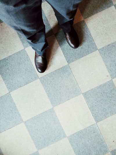Shoes in the Office Low Section High Angle View Human Leg Tiled Floor Flooring Close-up Human Foot Footwear Pair Feet Canvas Shoe Personal Perspective Dress Shoe Foot Tile Wooden Floor