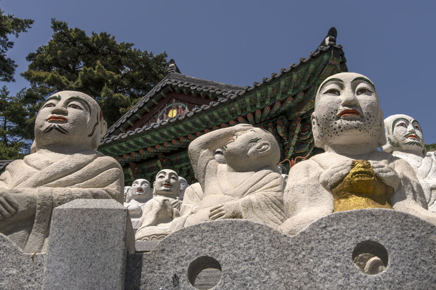 View of Bomunsa, a famous Buddhism temple at Seokmodo in Ganghwado, Kimpo, Gyeonggido, South Korea Bomunsa Buddhism Temple Seokmodo South Korea Architecture Art And Craft Belief Buddhism Built Structure Clear Sky Creativity Day Ganghwado Human Representation Low Angle View Male Likeness Nature No People Ornate Outdoors Place Of Worship Religion Representation Sculpture Sky Spirituality Statue Temple