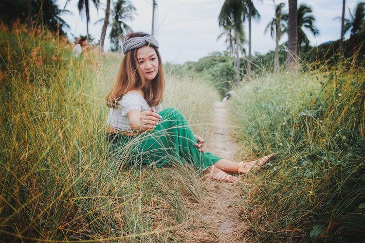Thoughtful woman sitting on grassy field