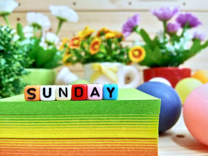 Close-up of colorful blocks with sunday text on stacked papers over table