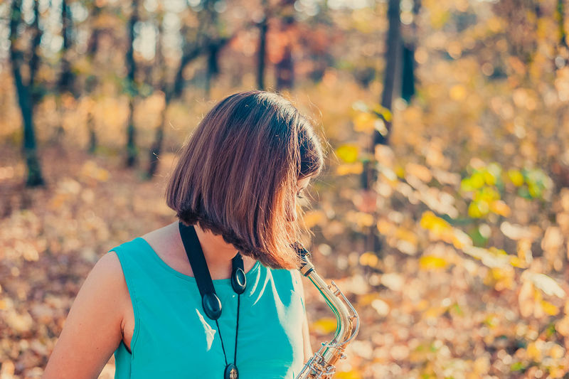 Midsection of woman with autumn leaves in forest