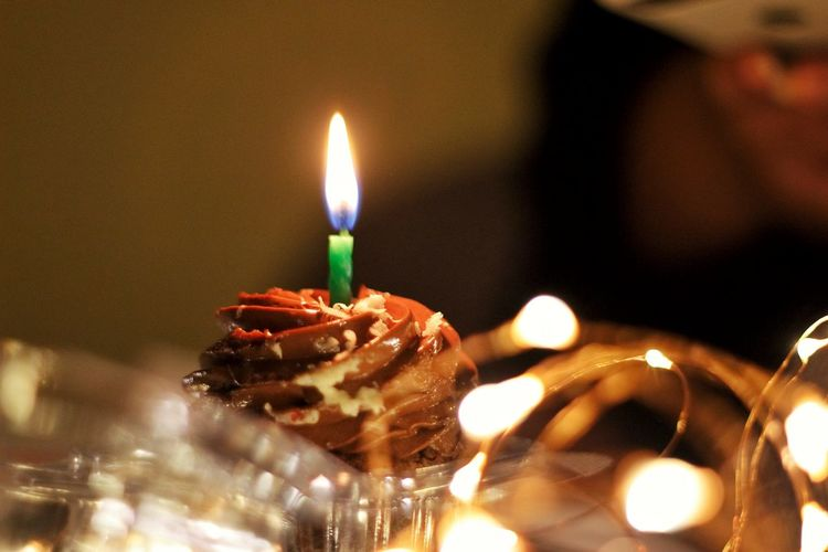 Close-up of burning candles on cake