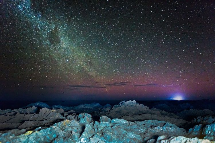 Scenic View Of Rocky Shore Against Sky With Star Field At Night