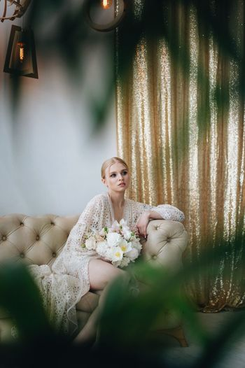 beautiful young blonde girl sits on the couch with a bouquet of light flowers holding in her hand One Person Beautiful Woman Women Beauty Young Adult Sitting Adult Luxury Portrait Wealth Furniture Young Women Fashion Relaxation Indoors  Hair Contemplation Clothing Blond Hair Hairstyle The Fashion Photographer - 2018 EyeEm Awards The Portraitist - 2018 EyeEm Awards