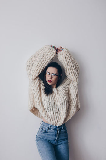 Portrait of young woman in stylish oversized sweater and mom jeans Beautiful Woman Beauty Casual Clothing Caucasian Fashion Fashion Model Front View Glasses Gray Background Hands Up Indoors  Jeans Lifestyles Mom Jeans One Person Oversized Portrait Standing Sweater Warm Clothing Women Young Adult Young Women