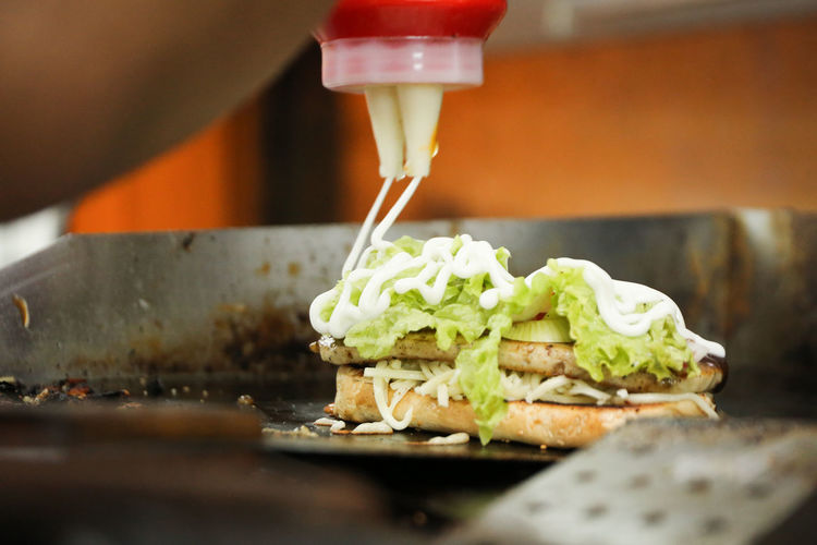 Cropped image of person making sandwich
