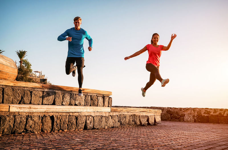 Full length of friends running and jumping while exercising together against clear sky