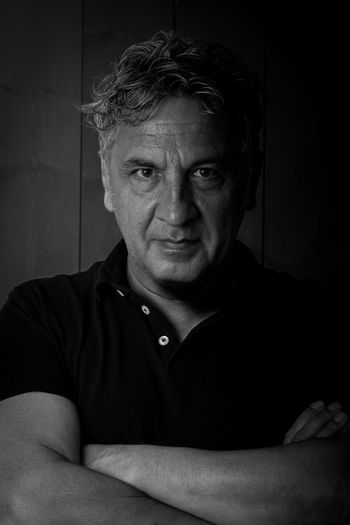 A man with a satisfied expression looks in front of the camera with his arms crossed Black & White Adult Black And White Blackandwhite Casual Clothing Close-up Contemplation Crossed Arms Front View Headshot Home Interior Human Face Indoors  Lifestyles Looking At Camera Males  Mature Adult Mature Men Men Mid Adult Mid Adult Men One Person Portrait Real People Satisfied
