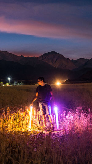 Man standing on illuminated field against sky at night