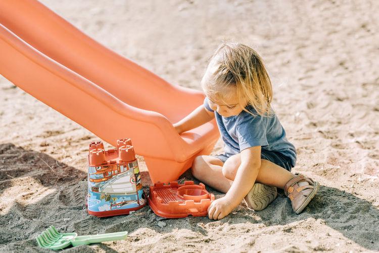 High angle view of girl sitting on sand