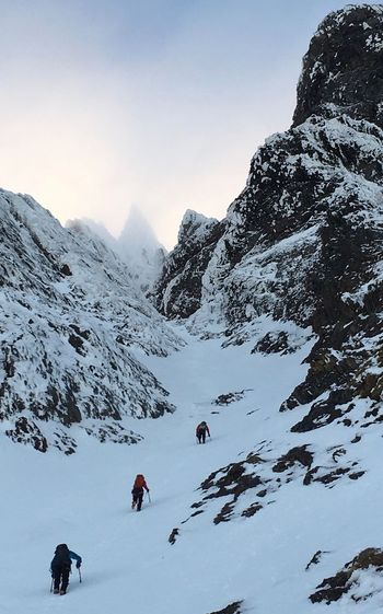 Low Angle View Of People Climbing On Snow Covered Mountain Against Sky