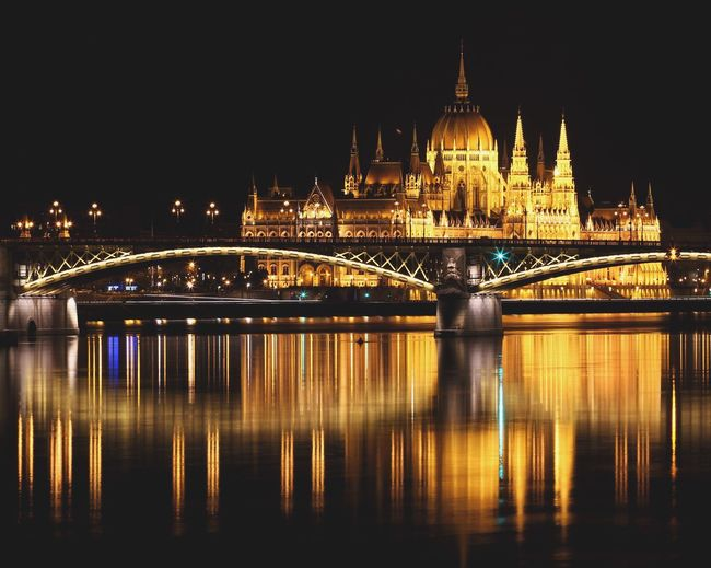 Bridge over river against illuminated hungarian parliament building at night