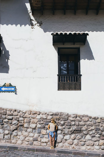 Full length of woman walking on wall of building