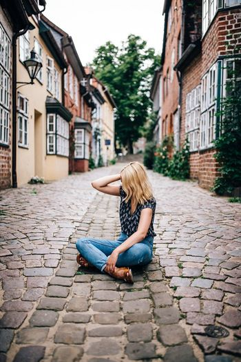 Full length of blond woman sitting on cobbled footpath amidst houses
