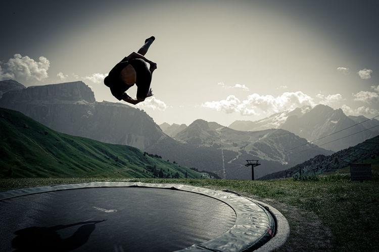 Man jumping on mountain range against sky