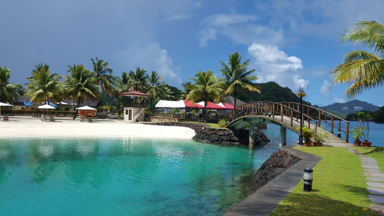 water, sky, tree, palm tree, tropical climate, built structure, architecture, plant, nature, day, sea, bridge, incidental people, building exterior, swimming pool, pool, connection, tourist resort, scenics - nature, outdoors, turquoise colored, coconut palm tree