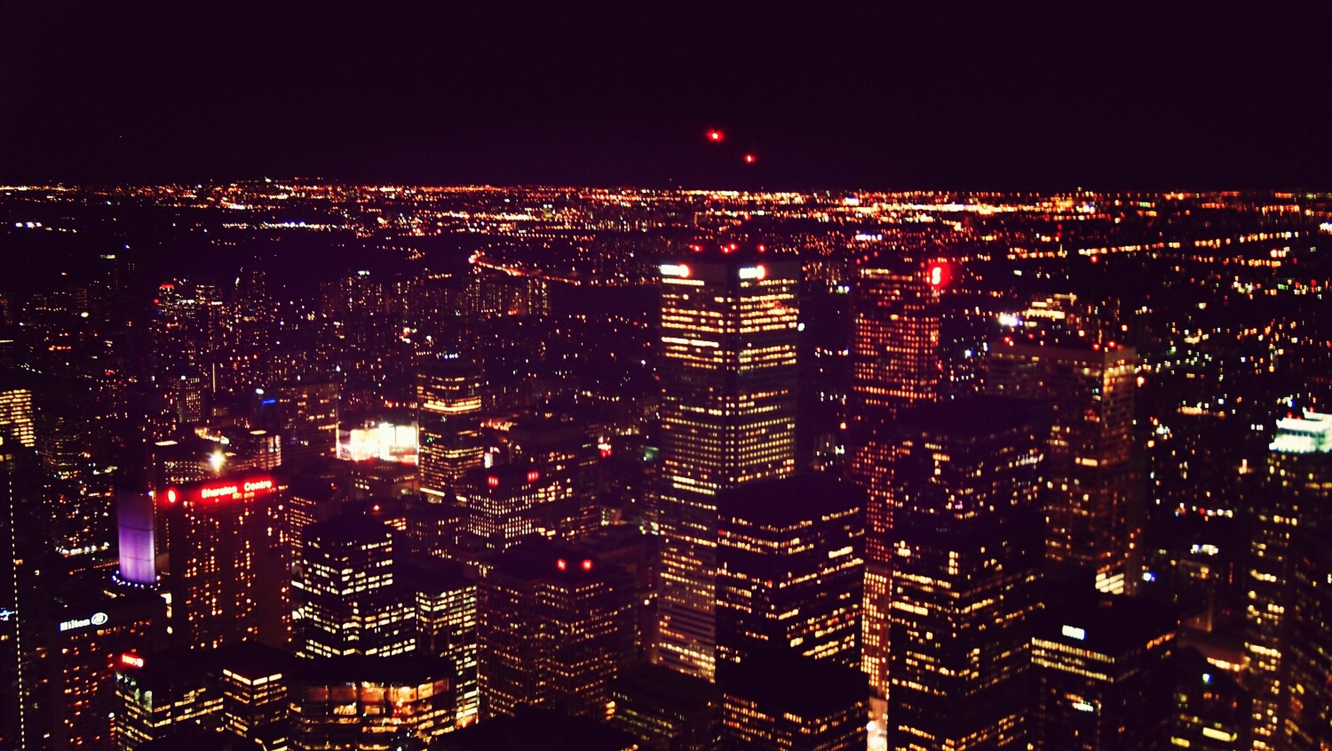 illuminated, night, cityscape, city, building exterior, architecture, crowded, built structure, high angle view, skyscraper, residential district, dark, sky, modern, aerial view, city life, light, residential building, no people, tower