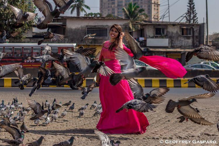 Woman flying birds against buildings in city