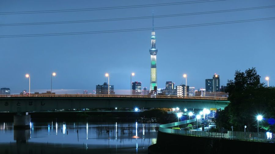 Bridge over river against illuminated tokyo sky tree at night