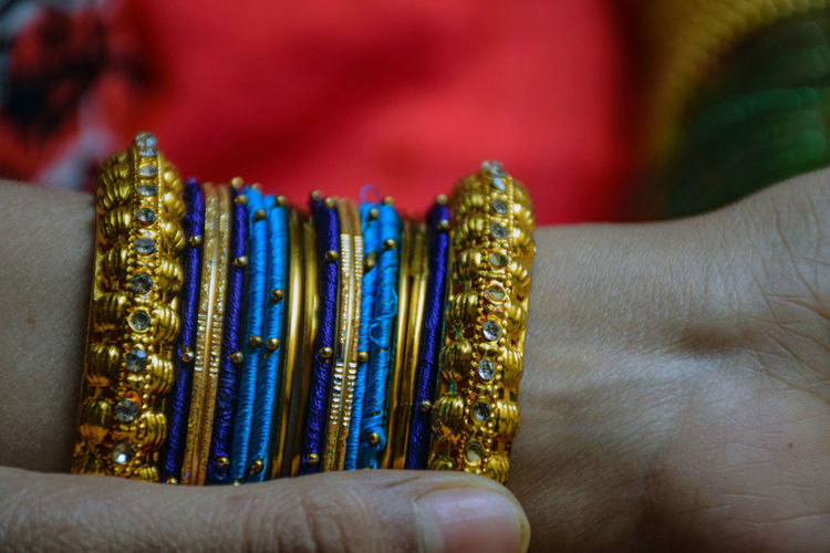 Side view of girl wearing colorful glass bangles