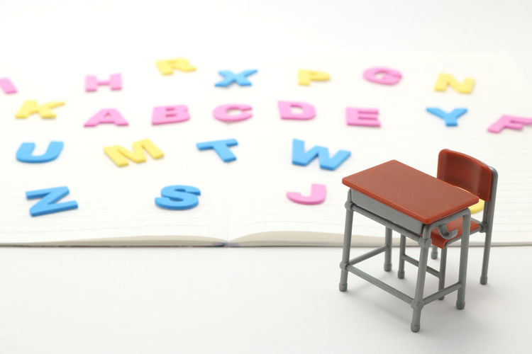 Close-up of miniature desk and chair with multi colored alphabets on book over white background