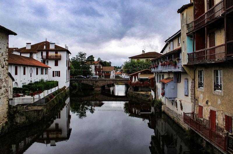 Canal amidst buildings against cloudy sky at saint-jean-pied-de-port