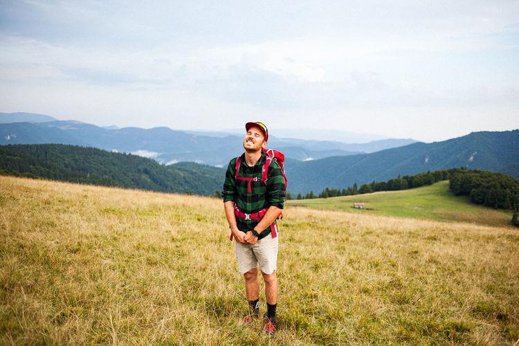 Smiling backpacker standing on mountain against sky