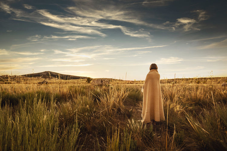 Rear view of woman looking at field against sky
