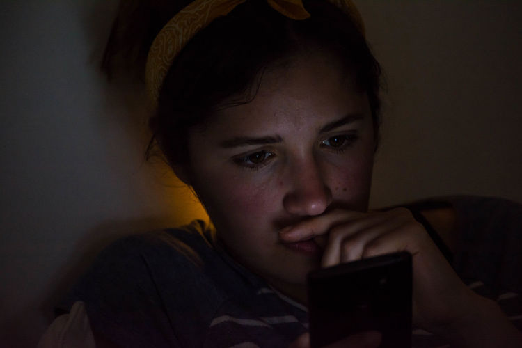 Close-Up Of Young Woman Using Mobile Phone At Home