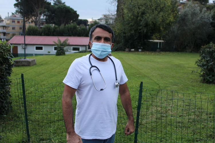 Male doctor with stethoscope and facemask outdoor