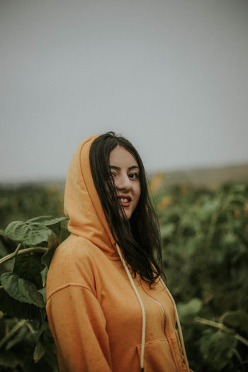 Portrait of young woman smiling while standing at sunflower farm
